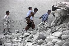 Выжившие после землетрясения идут среди развалин здания в городе Аваран 25 сентября 2013 года. Число погибших в результате землетрясения в Пакистане выросло в среду до 208 человек, сообщили чиновники. REUTERS/Sallah Jan