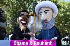 """Члены международной общественной организации """"Авааз"""" в масках Барака Обамы м Хасана Рухани у штаб-квартиры ООН в Нью-Йорке 24 сентября 2013 года. Президент США Барак Обама во вторник осторожно приветствовал шаг к примирению со стороны нового президента Ирана в качестве основы для возможного урегулирования проблемы вокруг ядерной программы Тегерана, но провалившаяся попытка добиться рукопожатия двух лидеров подтвердила, что преодолеть давнее недоверие будет сложно. REUTERS/Eduardo Munoz"""