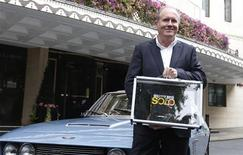 Author William Boyd poses for photographers with one of the first copies of his new James Bond book 'Solo,' in front of a Jensen car outside the Dorchester Hotel, both of which feature in the book, in London September 25, 2013. REUTERS/Suzanne Plunkett