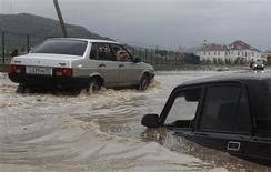 People take pictures of a car stranded in floodwaters along a flooded street in Sochi, September 25, 2013. REUTERS/Maxim Shemetov