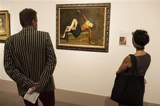 "A woman looks at the painting entitled ""Therese on a bench seat"" by French artist Balthus at the Metropolitan Museum of Art's ""Balthus: Cats and Girls Paintings and Provocations"" exhibition in New York September 23, 2013. REUTERS/Keith Bedford"