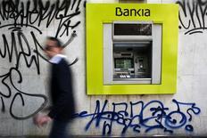 Imagen de archivo de un cajero automático del banco Bankia rodeado por rayados en Madrid, mayo 28 2013. La española Bankia está estudiando vender un 12 por ciento de la aseguradora Mapfre a través de un proceso conocido como colocación acelerada, dijo el miércoles una fuente con conocimiento de la operación. REUTERS/Susana Vera