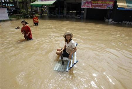 A woman sits on a bench in a flooded street at Srimahaphot district in Prachin Buri province, east of Bangkok September 24, 2013. REUTERS/Chaiwat Subprasom