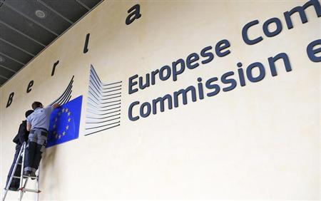 Workers adjust and clean the logo of the European Commission at the entrance of the Berlaymont building, the EC headquarters, in Brussels September 12, 2013. REUTERS/Yves Herman