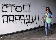 "A woman walks past a graffiti reading, ""Stop the parade"" in Belgrade September 26, 2013. REUTERS/Marko Djurica"