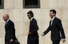 Barcelona's soccer player Lionel Messi (R) leaves after answering charges of tax evasion in a court in Gava September 27, 2013. REUTERS/Albert Gea