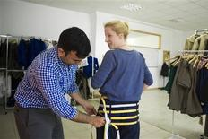 Asaf Moses (L), co-founder of clothes sizing software start-up UPCload, demonstrates a customised pair of trousers used to take body measurements at the UPCload office in Berlin August 21, 2013. REUTERS/Thomas Peter