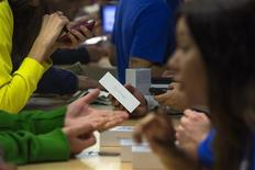Un grupo de clientes compra el teléfono iPhone 5s de Apple en una tienda de la firma en la quinta avenida de Manhattan, sep 20 2013. El gasto de los hogares en Estados Unidos subió en agosto debido a que los ingresos aumentaron a su mayor ritmo en seis meses, señales de que podría estar creciendo el impulso en la economía estadounidense, pese a varios meses de dura austeridad gubernamental. REUTERS/Adrees Latif