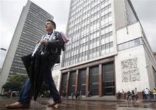 Un hombre camina a las afueras del Banco Central de Colombia en Bogotá, mar 1 2011. El Banco Central de Colombia inició el viernes su reunión de política monetaria en momentos en que algunos sectores presionan por un recorte de tasas, pero los recientes datos que mostraron a una economía más vigorosa de lo pronosticado alejarían esa posibilidad. REUTERS/John Vizcaino