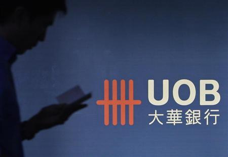 A man passes a logo of United Overseas Bank in the central business district in Singapore, April 29, 2013. REUTERS/Edgar Su