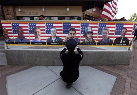 San Diego firefighter Robert Bunsoldat takes a picture of each of the Prescott Fire Department's Granite Mountain Hotshots team from a banner that circles the entrance to their memorial in Prescott Valley, Arizona July 9, 2013. REUTERS/Mike Blake