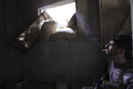 A Free Syrian Army fighter smokes while monitoring an area through a mirror inside a room in Deir al-Zor September 28, 2013. REUTERS-Khalil Ashawi