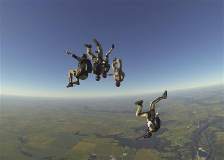 The Arizona Arsenal skydive team jumps during the National Skydiving Championships in Ottawa, Illinois in this handout picture taken September 13, 2013. The job of professional skydiver Brandon Atwood is to look back up to the sky, point a camera attached to his helmet and record on video four teammates performing a complex skydiving routine. Without Atwood, no one on the ground would see the Arizona Arsenal's winning performance in the 4-person vertical formation skydiving event at the U.S. National Skydiving Championships near Chicago earlier this month. REUTERS/Amy Chmelecki/United States Parachuting Association/Handout via Reuters