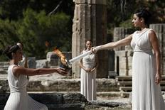 Greek actress Ino Menegaki (R), playing the role of High Priestess, passes the Olympic flame to a priestess during a lighting ceremony of the Sochi 2014 Winter Olympic Games at the site of ancient Olympia in Greece September 29, 2013. REUTERS/Yorgos Karahalis