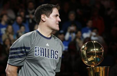 Dallas Mavericks owner Mark Cuban holds the Larry O'Brien Championship trophy during a ceremony before their NBA basketball game with the Miami Heat in Dallas, Texas December 25, 2011. REUTERS/Mike Stone