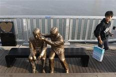 A man walks past a statue of a person comforting another on the Mapo Bridge, one of 25 bridges over the Han River, in central Seoul September 27, 2013. REUTERS/Lee Jae-Won