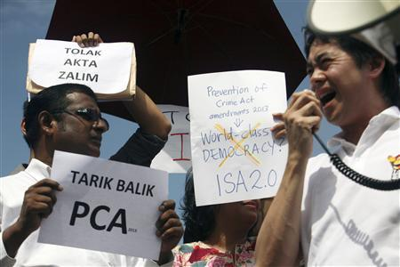 Members of non-government organisation (NGO) SUARAM (Suara Rakyat Malaysia) hold up placards during a protest against the new amendments in the Prevention of Crime Act (PCA) which resurrects back the detention without trial, outside the parliament house in Kuala Lumpur September 30, 2013. The placards read: ''Abolish PCA'' (front L) and ''Against cruel act'' (back L). REUTERS/Samsul Said