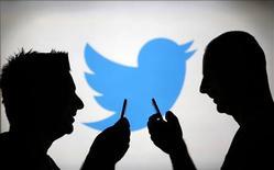 Unos hombres posan contra una pantalla de video con el logo de Twitter en Zenica, Bosnia y Herzegovina, ago 14 2013. Twitter planea su salida a bolsa a finales de esta semana, informó el domingo la página web de noticias Quartz, citando una persona familiarizada con los planes de la red social. REUTERS/Dado Ruvic