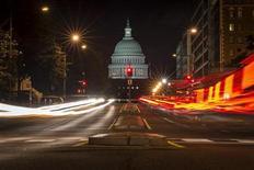 Светофор на фоне здания Капитолия в Вашингтоне 30 сентября 2013 года. Администрация США впервые за 17 лет оказалась вынуждена частично приостановить работу, в результате чего около одного миллиона служащих могут быть отправлены в неоплачиваемый отпуск, национальные парки закрыты, а медицинские исследовательские проекты - прерваны. REUTERS/James Lawler Duggan