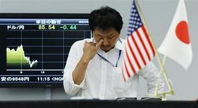 Валютный дилер стоит у экрана с графиком изменений курса японской иены к доллару США в трейдинговой компании в Токио 4 августа 2010 года. Если Конгресс США не разрешит повысить долговой потолок страны в ближайшие недели, она окажется на грани беспрецедентного дефолта. Но главные кредиторы США в Азии, вероятно, окажутся наименьшей из их проблем. REUTERS/Yuriko Nakao