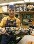 Официантка с тарелками гюдона в ресторане сети Yoshinoya в Токио 18 сентября 2006 года. Большая японская сеть фастфуда планирует выращивать ингредиенты в префектуре Фукусима, примерно в 100 километрах от одноименной аварийной атомной электростанции, выход которой из строя в 2011 году вызвал худший ядерный кризис на планете с Чернобыльской аварии 1986 года. REUTERS/Michael Caronna