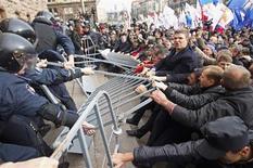 Демонстранты в Киеве вырывают металлические барьеры у милиционеров 2 октября 2013 года. Украинская милиция в среду применила слезоточивый газ, отгоняя группу протестующих, пытавшихся прорваться в мэрию столицы, сообщили МВД и оппозиционные активисты. REUTERS/Valentyn Ogirenko