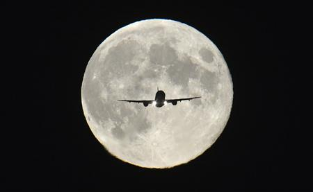 A passenger aircraft, with the full ''Harvest Moon'' seen behind, makes its final approach to landing at Heathrow Airport in west London, September 19, 2013. REUTERS/Toby Melville