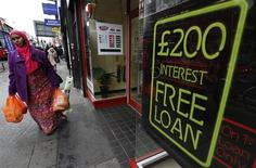 Una mujer pasa junto a una casa de préstamos monetarios en Londres, oct 3 2013. El crecimiento en la economía global cayó en septiembre a su nivel más bajo en tres meses frenado por un moderado desempeño de las empresas en Estados Unidos, de acuerdo a un sondeo de negocios divulgado el jueves. REUTERS/Suzanne Plunkett