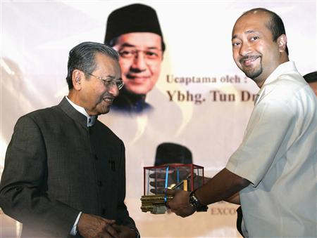 Malaysia's elected member of parliament Mukhriz Mahathir (R) receives a memento from his father, former Malaysian Prime Minister Mahathir Mohamad, after a meeting in Petaling Jaya outside Kuala Lumpur in this April 1, 2008 file photo. REUTERS/Bazuki Muhammad/Files