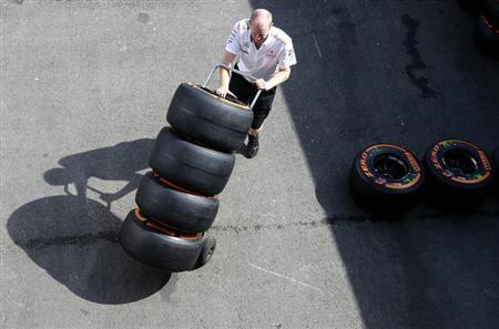 A McLaren Formula One technician pushes a trolley with Pirelli tyres ahead of the weekend's Belgian F1 Grand Prix in Spa-Francorchamps August 22, 2013. REUTERS/Francois Lenoir