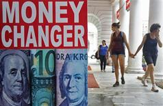 Туристы проходят мимо пункта обмена валют в Дели 20 августа 2013 года. Евро остается вблизи максимального уровня, достигнутого в 2013 году, благодаря притоку положительных новостей из еврозоны и слабости доллара, обусловленной продолжением безрезультатных споров о федеральном бюджете США. REUTERS/Anindito Mukherjee