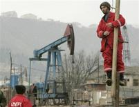 Рабочие на фоне нефтяного станка-качалки в Баку 17 марта 2009 года. Цены на нефть снижаются из-за опасений, что закрытие государственных учреждений США плохо отразится на потреблении нефти. REUTERS/David Mdzinarishvili