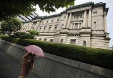 A pedestrian holding an umbrella walks past the Bank of Japan headquarters in Tokyo August 8, 2013. REUTERS/Yuya Shino
