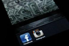 Экран iPhone с окошками приложений Facebook и Instagram в Загребе 9 апреля 2012 года. Миллионы пользователей Instagram в ближайшие пару месяцев увидят рекламу в своих фотолентах. REUTERS/Antonio Bronic