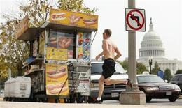 Мужчина пробегает мимо уличной палатки, торгующей хот-догами, недалеко от здания Капитолия в Вашингтоне 3 октября 2013 года. Пока политики в Вашингтоне безуспешно ищут пути выхода из тупика, временно оставившего без работы сотни тысяч американцев, на выручку последним пришли владельцы ресторанов, баров, фитнес-залов и даже компания, организующая прыжки с парашютом. REUTERS/Kevin Lamarque