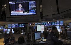 """La Reserva Federal de Estados Unidos confundió a los mercados financieros este año al publicar una serie de declaraciones """"confusas y contradictorias"""" sobre política monetaria, según un panel interno de asesores que instó al banco central a hacer un mejor trabajo de comunicación en el futuro. En la foto de archivo, operadores en la Bolsa de Nueva York viendo un discurso del presidente de la Fed, Ben Bernanke. Sep 18, 2013. REUTERS/Brendan McDermid"""