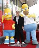 """Foto de archivo de Matt Groening, creador de """"The Simpsons"""", parado junto a la estrella en el Paseo de la Fama en Hollywood junto a Homero y Bart Simpson. Febr 14, 2012. REUTERS/Mario Anzuoni"""