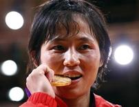 North Korea's An Kum Ae bites her gold medal as she celebrates during the awards ceremony for the women's -52kg judo competition at the London 2012 Olympic Games July 29, 2012. REUTERS/Darren Staples
