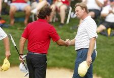 Phil Mickelson of the U.S. (L) shakes hands with International team player Ernie Els of South Africa after Mickelson and playing partner Keegan Bradley won their four ball match against Els and Brendon de Jonge of Zimbabwe at the 2013 Presidents Cup golf tournament at Muirfield Village Golf Club in Dublin, Ohio October 5, 2013. REUTERS/Chris Keane