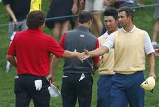 Jason Dufner (L) of the U.S. shakes hands with Adam Scott (R) of Australia as Zach Johnson of the U.S. shakes hands with Hideki Matsuyama of Japan after the International team of Scott and Matsuyama won their rain-delayed foursome match at the 2013 Presidents Cup golf tournament at Muirfield Village Golf Club in Dublin, Ohio October 5, 2013. REUTERS/Jeff Haynes (UNITED STATES - Tags: SPORT GOLF)