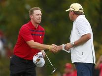 Hunter Mahan of the U.S. (L) shakes hands with International team captain Nick Price of Zimbabwe after he and Brandon Snedeker defeated International team players Louis Oosthuizen and Charl Schwartzel, both of South Africa, in their four ball match at the 2013 Presidents Cup golf tournament at Muirfield Village Golf Club in Dublin, Ohio October 5, 2013. REUTERS/Chris Keane