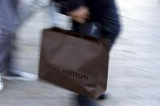 A man walks with a Louis Vuitton shopping bag as he leaves a Louis Vuitton store in Paris September 24, 2013. REUTERS/Philippe Wojazer