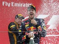 Second placed Lotus Formula One driver Kimi Raikkonen of Finland (L) sprays champagne at winner Red Bull Formula One driver Sebastian Vettel of Germany on the podium after the Korean F1 Grand Prix at the Korea International Circuit in Yeongam, October 6, 2013. REUTERS/Kim Hong-Ji
