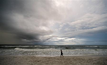 A beachgoer takes an early morning walk as storm clouds from a weakening Tropical Depression Karen approach Orange Beach, Alabama, October 6, 2013. REUTERS/Steve Nesius