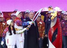 Russian President Vladimir Putin (C), Russian ice-skaters Lina Fyodorova (L), 16, of Moscow and Maksim Miroshkin (2nd L), 19, of Ekaterinburg light an Olympic torch during a ceremony to mark the start of the Sochi 2014 Winter Olympic torch relay in Moscow October 6, 2013. REUTERS/Sergei Karpukhin