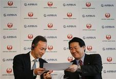 Japan Airlines President Yoshiharu Ueki (R) exchanges documents with Airbus Chief Executive Fabrice Bregier during their joint news conference in Tokyo October 7, 2013. REUTERS/Toru Hanai