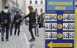 Женщина просит подаяния на фоне таблички обменного пункта в Москве 1 июня 2012 года. Рубль подешевел в понедельник из-за США и улучшения ситуации на денежном рынке. REUTERS/Denis Sinyakov