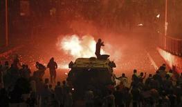 """Сотрудник полиции на бронетраспортере в окружении противников экс-президента Египта Мохамеда Мурси ведет огонь по членам """"Братьев-мусульман"""" и сторонникам Мурси во время массовых беспорядков в Каире 6 октября 2013 года. Не менее 50 человек погибли в ходе столкновений сторонников и противников свергнутого президента Египта Мохамеда Мурси в воскресенье, сообщили источники в силах безопасности страны. REUTERS/Amr Abdallah Dalsh"""