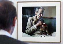 David Dawson, who worked with British painter Lucian Freud at Freud's studio and home for over 20 years, looks at one of his photographs of the artist during an interview with Reuters at the Sigmund Freud museum in Vienna October 7, 2013. REUTERS/Heinz-Peter Bader