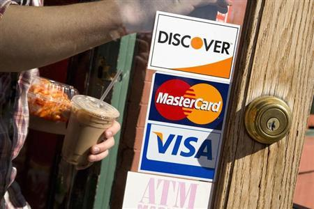 A coffee shop displays signs for Visa, MasterCard and Discover, in Washington, May 1, 2013. REUTERS/Jonathan Ernst